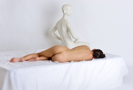 Beautiful naked sexy woman laying on white bed. View from a back side. The , mannequin sitting on the same bed.