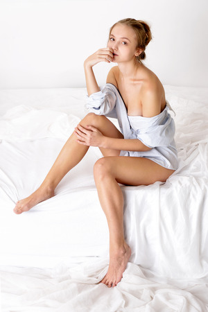 nude woman sitting: Beautiful sexy woman in shirt sitting on white bed. Studio shooting with white background.