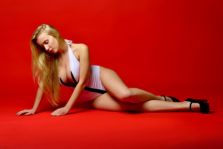 Beautiful blonde woman in lingerie lying on the floor in studio with red background.