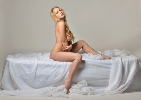 nude girl sitting: Beautiful naked sexy blonde woman sitting on white bed.