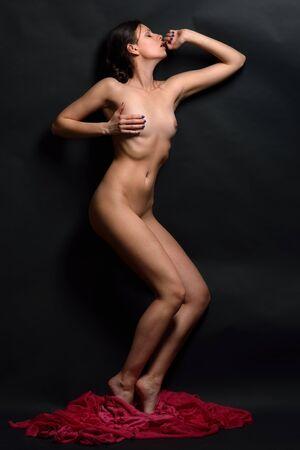 femme nu sexy: Belle femme sexy nue posant en studio avec un fond sombre. Photo Concept avec une corde rouge.