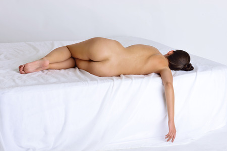 sex pose: Beautiful naked sexy woman laying on white bed. View from a back side.