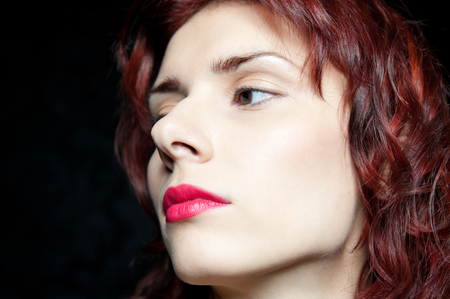 Torso portrait of the beautiful woman with red hair and red lips in studio with dark background. photo