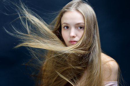 Portrait of the beautiful blonde woman with flying long hair. She is with naked shoulders  in studio . Stock Photo