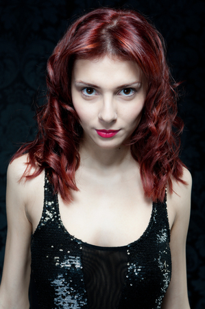 Torso portrait of the beautiful woman with red hair and black top in studio with dark background. photo