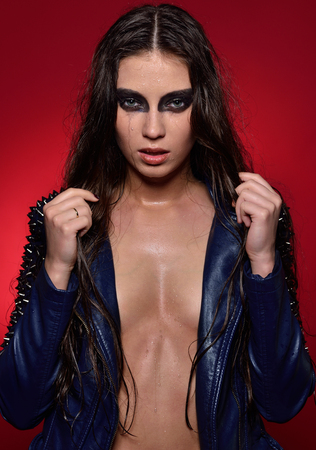 Portrait of the beautiful woman with wet stage make up. Rock shape in leather jacket and panties.