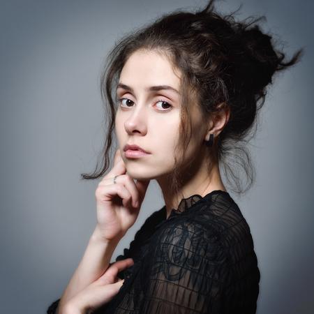 schöne Frau mit Kurvenhaar und Tätowierung in der schwarzen transparenten Bluse, die im Studio aufwirft.