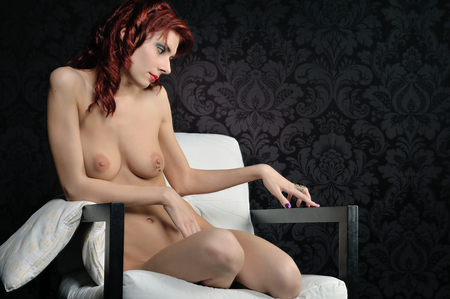 Young beautiful naked woman with red hair and lips sitting on the armchair. Studio with dark background Stock Photo