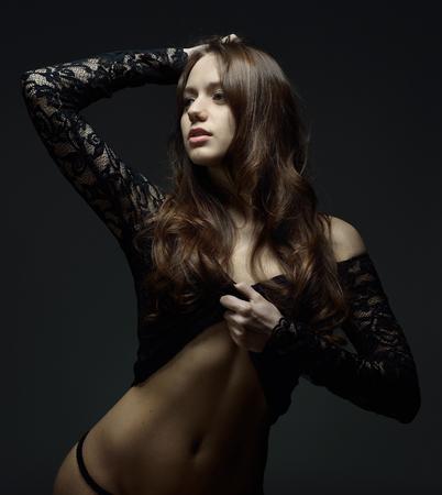 Portrait de torse de la belle femme aux longs cheveux bruns en lingerie en dentelle. Studio avec fond sombre.