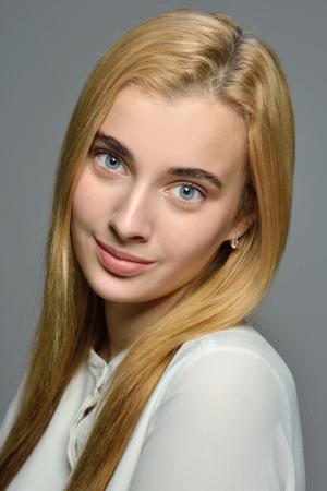 Portrait de la belle femme blonde aux cheveux longs en blouse blanche. Prise de vue en studio sur fond gris. Maquillage naturel.