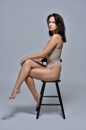 Beautiful woman in underwear sitting on the chair. Studio with grey background.