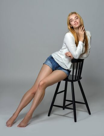 beautiful barefoot woman in jeans shorts and white shirt. She is sitting on high chair in studio with gray background.