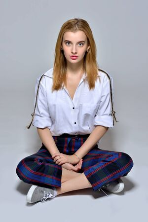 Sitting portrait of the beautiful blonde woman in white shirt and  checked trousers. Studio shooting.