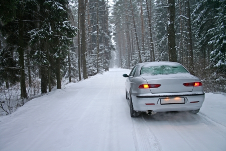 winter road: car in a snowy winter forest Stock Photo