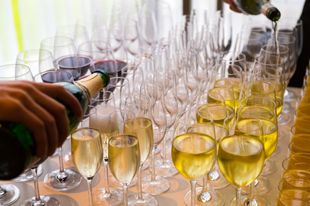 waiters poured into glasses of wine and champagne photo