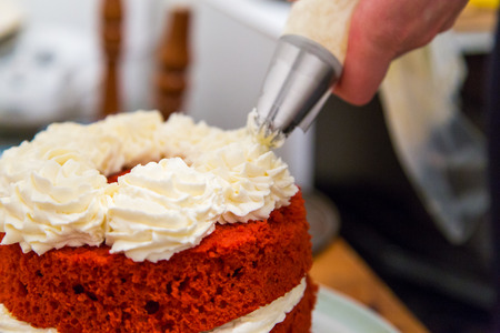 Close-up hand decorating red velvet cake with whipped cream Фото со стока