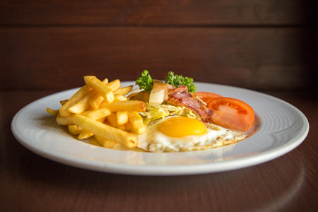 bacon and eggs: breakfast with fried potato bacon eggs and tomato on wooden background