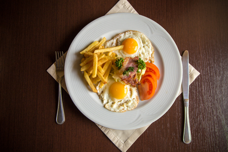 bacon and eggs: american breakfast with fried potato bacon eggs and tomato