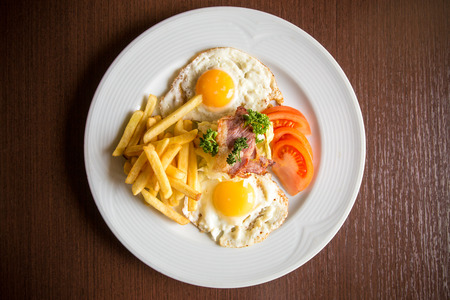 bacon and eggs: closeup american breakfast with fried potato bacon eggs and tomato on wooden background