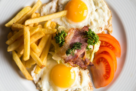 bacon and eggs: closeup american breakfast with fried potato bacon eggs and tomato