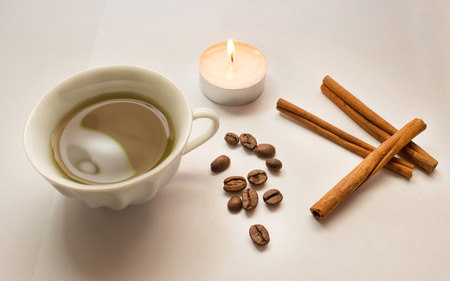 cinnamon sticks, coffee beans, lighted candle, a cup of coffee on a white background