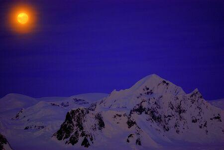 Moon on the dark blue sky among mountains. Antarctica. Stock Photo - 10276451