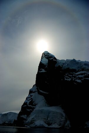 The sun peeps out from the edge of the clouds. On the horizon are visible icebergs Stock Photo - 10276250