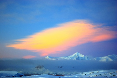 Covered with white snow mountain covered with clouds at sunset in Antarctica photo