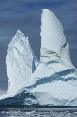 A large iceberg with two peaks floating in the ocean. Imagens