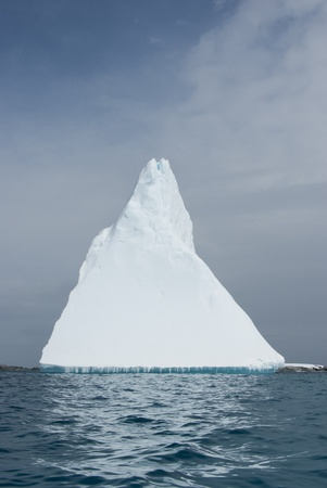 Iceberg in the form of a pyramid in the ocean.