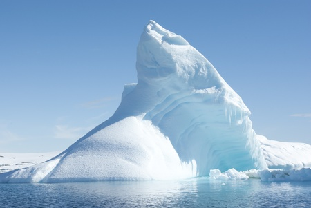 Icebergs in the sunny bright light on the background of the island. photo