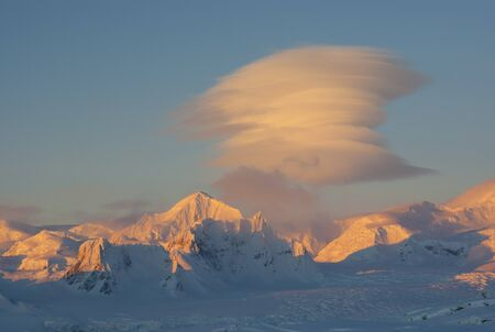 lenticular: Lenticular clouds over the mountains of Antarctica. Stock Photo