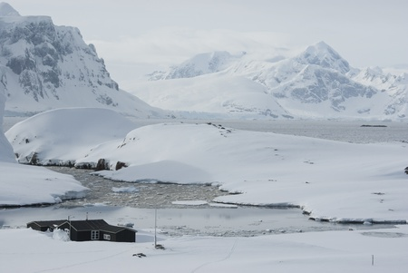 The Antarctic winter station on the background of mountains and ocean.