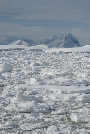 The mountains of the Antarctic winter in the background covered with ice of the strait.