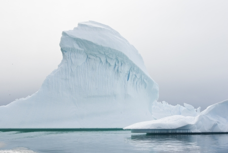 Iceberg in Antarctic waters on a cloudy summer day. Stock Photo