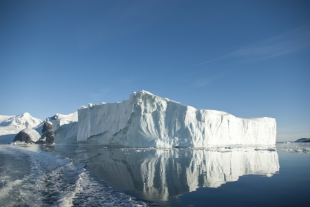Large iceberg and its reflection in the southern ocean on a summer day. Stock Photo