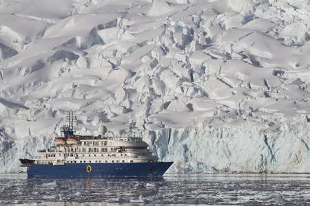 antarctic peninsula: blue tourist ship on the background of a summer day glaciers of the Antarctic Peninsula Stock Photo