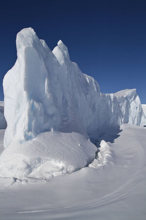 steep side of the dome of the iceberg that is frozen in Antarctic waters