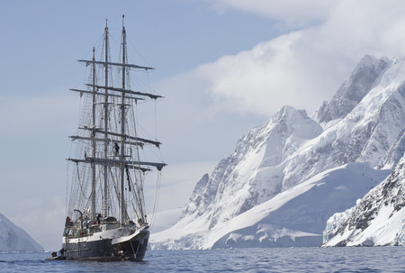 tourist ship sailing summer day on a background of mountain peaks of the Antarctic Peninsula