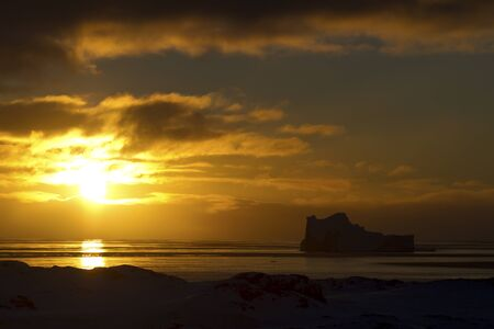 iceberg and waters of the southern ocean at sunset in Antarctica