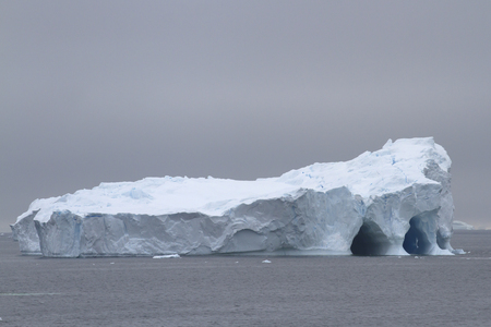 large flat iceberg with several caves Stok Fotoğraf