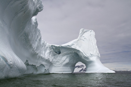 large iceberg with a through arch in Antarctic waters