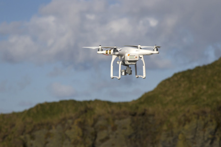 drones: small unmanned helicopter with a camera flying in the blue sky above the hills