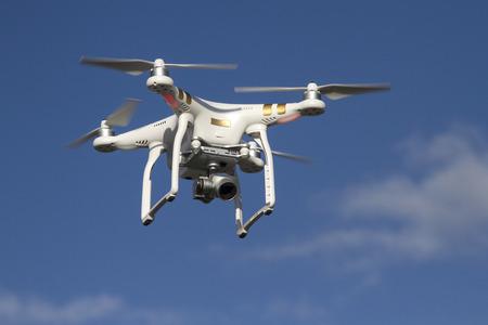 kleine unbemannte Hubschrauber mit einer Kamera in den blauen Himmel fliegen Standard-Bild