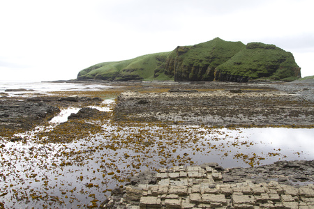 island cape at low tide and a slab that opens from the water which separates it from the shore