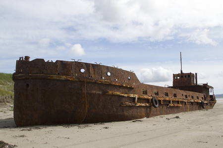 The old barge thrown on the sandy shore Stock Photo