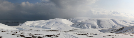 panorama of the winter tundra floodplain of the river flowing between the snow-covered hills to the ocean