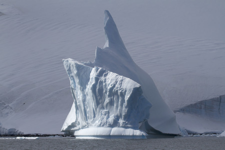 iceberg with a high arrow top near the Antarctic coast on a cloudy day Reklamní fotografie