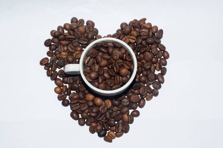 White porcelain cup stands in coffee beans in the shape of heart Stock Photo