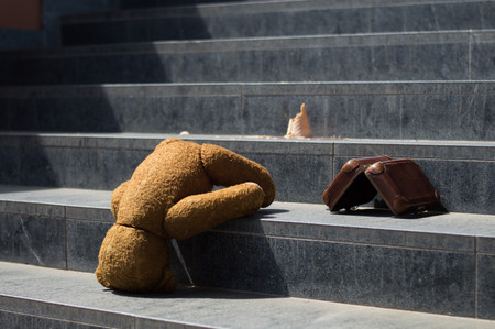 misadventure: Travel teddy bear fell down on the stairs with ice cream and his suitcase Stock Photo